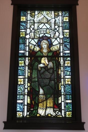 エントランスに入ると正面に見えるのが「聖女マグダラのマリア」。19世紀後半、イギリスのジェームズ・パウエル&サンズ工房で制作されたもので、聖女の顔や服装だけでなく、背後に描かれる建築装飾や、ダイヤ型に組まれた背景の文字装飾など、当時の最高技術で製作された作品です。