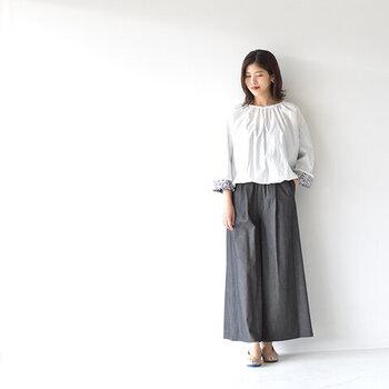 適度なハリと光沢感のあるデニムワイドパンツを、白ブラウスと合わせて上品な着こなしに。足元はベージュのパンプスで、カジュアルさを抑えたコーディネートにまとめています。