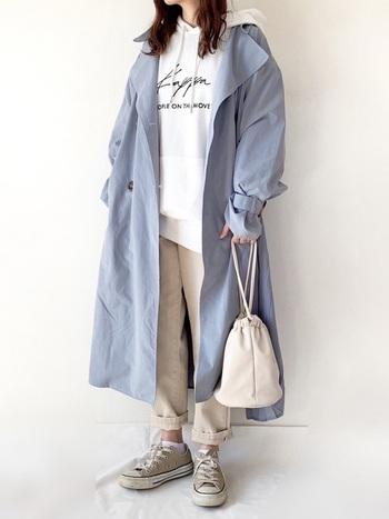くすみブルーのトレンチコートに、ロゴ入りの白パーカを重ねたスタイイリング。オフホワイトやベージュ系でまとめて爽やかに着こなしています。