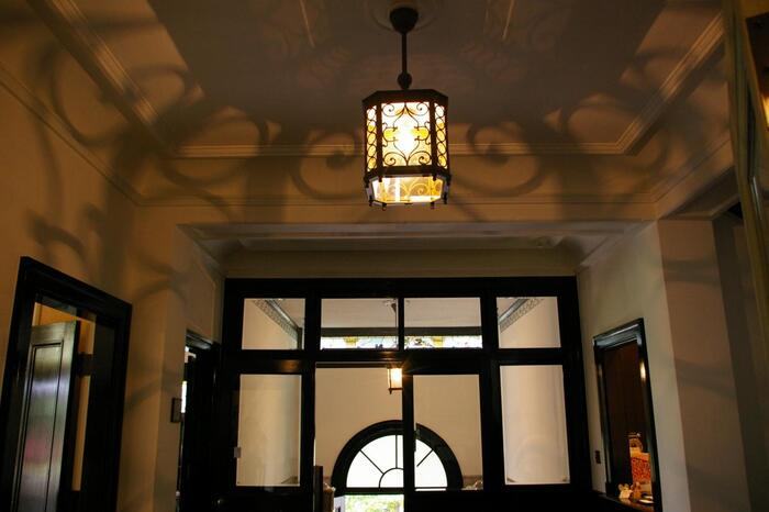 建築内部の見所は、応接・居間・食堂の三部屋。照明器具や家具、美術品といった調度品も上品で素晴らしいですが、部屋それぞれには、床、壁面、天井と随所に細やかな工夫が凝らされ、様々なスタイルでデザインされています。 【ランプシェードの影も美しい邸内「玄関ホール」】
