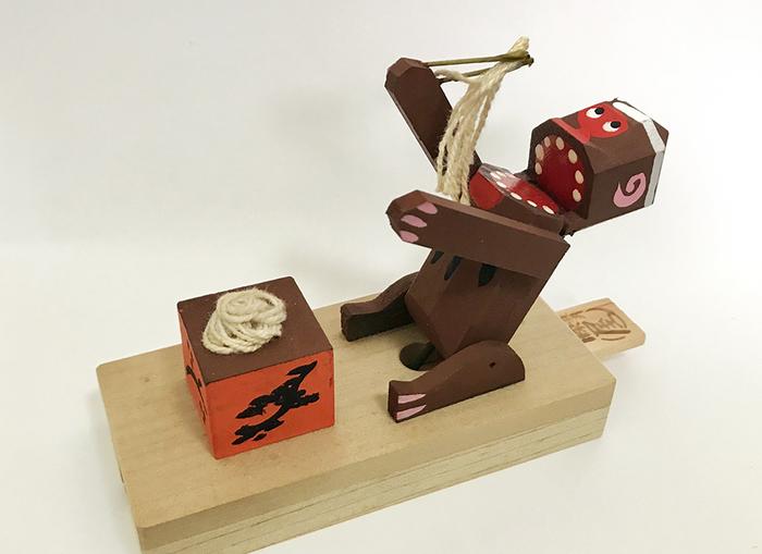長野県木曽郡、奈良井宿のそば喰い猿は、ユーモラスな動きが魅力的なカラクリ玩具。  後ろ側にある木の取っ手を引いたり、押したりすると、猿が大きな口を開けてそばを食べます。シンプルな構造ですが、何度見ても、可愛らしく、ほっこりとした気分になれる玩具です。