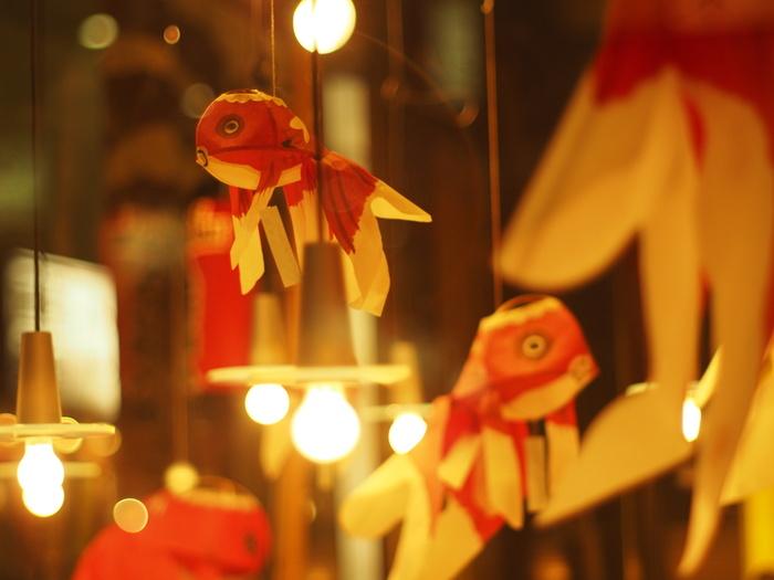 「金魚提灯(きんぎょちょうちん)」とは、山口県柳井市に伝わる金魚提灯は全国民芸品番付でも上位にランキングされたこともある知名度の高い郷土玩具です。  明治時代に、柳井の織物職人が竹ひごを使った紙細工に織物の染料を使って作り始めました。青森の金魚ねぶたをもとに作られたそう。大きなしっぽがゆらゆらと揺れて、優雅な雰囲気を醸し出しています。