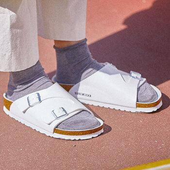 マットなホワイトカラーのアッパーにシルバーのバックルがポイント。足の甲が広範囲で覆われているので、寒々しい印象にならずに、靴下と合わせてシューズライクに使えます。