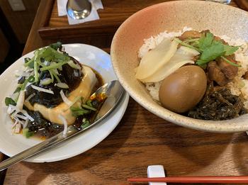 まず、台湾グルメではずせない魯肉飯(ルーローハン)をどうぞ。  八角の香りを味わいながら、お好みでお店のオリジナルラー油もプラスして。そのほか、にんにくや味噌といった調味料も置かれており、自分好みに味わいを調整できるのが嬉しいですね。  左側にあるのはピータン豆腐ですよ。