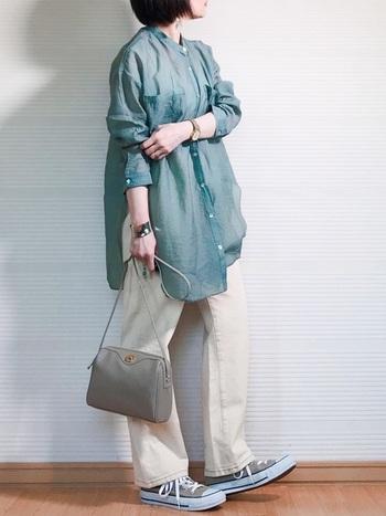 グリーンのゆったりシャツに、ベージュのパンツとスニーカーを合わせたカジュアル×フェミニンなスタイリング。シャツの透け感やショルダーバッグで、きちんと女性らしさをアピールしているのがポイント。