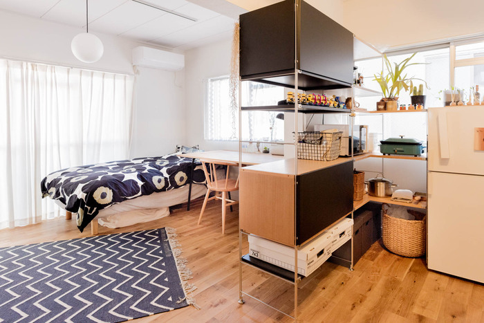 仕切りのないワンルームも、上手に仕切ってより住みやすく。向こう側が見える棚をパーテーション代わりに使って、生活スペースとキッチンを分割。完全に分断させないことで、開放感をキープしています。インテリアにメリハリをつけながら、収納スペースも確保できて一石二鳥です♪