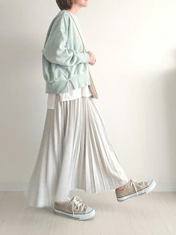 グレーカラーのプリーツスカートに、春コーデにぴったりな薄いグリーンのスウェットトップスを合わせたコーディネート。ベージュのスニーカーで、プリーツスカートを上手にカジュアルダウンしています。白インナーを裾からさりげなくチラ見せして、今っぽい着こなしに。
