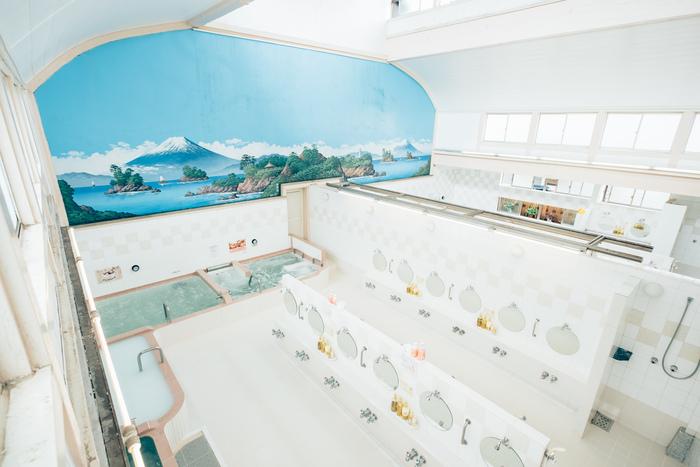 浴室内は白を基調とした明るい空間。壁に描かれた美しい富士山に心が洗われます。名物のミルク風呂や水風呂、日替わり湯や週替わり湯など、多彩なお風呂を楽しめるのも「小杉湯」の魅力です。