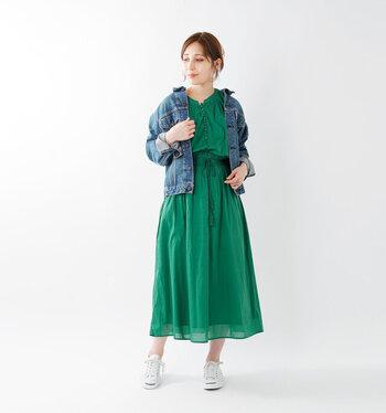 コットン素材で軽やかなグリーンのワンピース。デニムジャケット&スニーカーであえてカジュアルダウン。