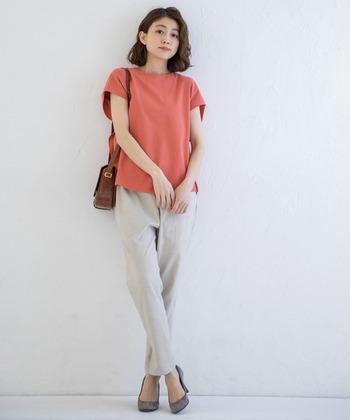 サーモンピンクの半そでシャツ。甘い雰囲気になりすぎないように、パンツはベージュでシンプルに着こなして。