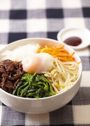 ナムルはいろいろな料理に使われますが、代表格はビビンバですね。ご飯の上に、もやし・にんじん・ほうれん草などのナムルや牛肉の韓国風炒めなどをきれいに盛り付け、中央に温泉卵をトッピング。コチュジャンを添えてどうぞ。