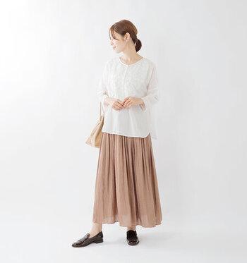 胸元にレースを贅沢にあしらった白ブラウスに、ベージュのロングスカートを合わせたナチュラル×フェミニンなコーディネートです。ブラウスはあえてタックインせず外に出すことで、大人のゆとりを感じさせるスタイリングに。足元は素足にローファーシューズで、抜け感をアピール。