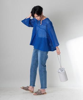スクエア刺しゅうを施したブルーのレースブラウスに、薄色のデニムパンツを合わせたコーディネート。フェミニン感のあるフレアブラウスなので、あえて裾が切りっぱなしのデニムをチョイスして甘辛バランスのとれたコーディネートに。