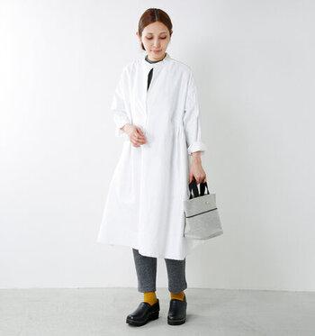 白のシャツワンピースにグレーのパンツを合わせて、ナチュラルにまとめたコーディネート。足元は黒のサボサンダルとマスタードカラーの靴下で、ベーシックな着こなしにアクセントをプラスしています。