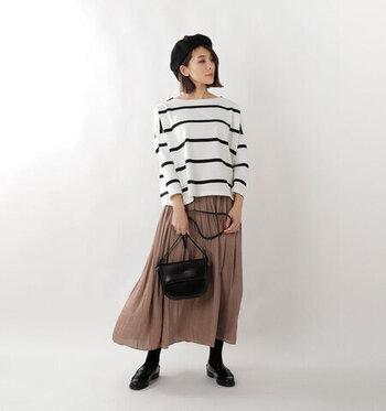 幅広めのボーダートップスに、茶色のロングスカートを合わせたレディライクなコーディネートです。バッグやシューズ、ベレー帽などの小物は全て黒でまとめて、スッキリとした印象に仕上げています。