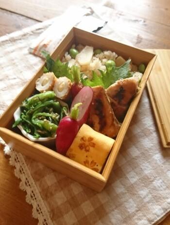 四角い一段弁当に、たけのこごはんを詰めて。鮭の西京焼きや、野菜も卵もバランスよく入れて、お腹も体も喜ぶ1箱に。
