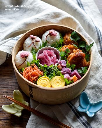 丸いお弁当箱は、中心に丸い容器を置いて簡単に仕切り作りを、その周りを埋めるようにして詰めると綺麗に収まりますよ♪いつものおにぎりの上に桜の塩漬けを飾ればそれだけで春色弁当に!