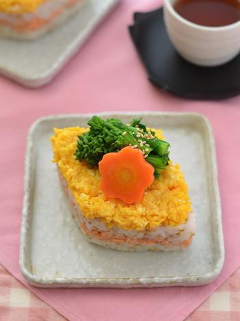 ■おもてなしご飯 【ひし餅風ちらし寿司】  鮭フレーク、炒り卵、菜の花、にんじんで作るひし餅風ちらし寿司。ちらし寿司は簡単なのにご馳走感があるメニューなので、おもてなしにぴったり!菜の花は一目で季節を感じてもらうために一番上に。