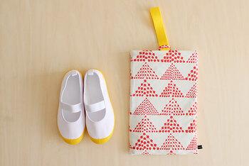 こちらは裏地ありのケース。2枚の表布を縫い合わせ、裏布は持ち手とループを縫い付けます。表布と裏布を合体させ、脇を縫って裏返したらもう一息!返し口を縫って裏布を中に押し込んだら完成です。20cm程度の上履きがすっぽり入ります。