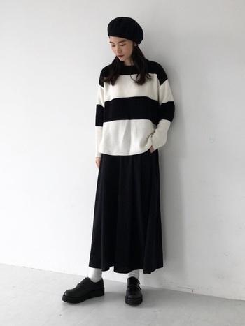「H&M(エイチアンドエム)」の幅広白黒ボーダーニットに、黒のロングスカートを合わせたモノトーンコーディネートです。白靴下以外は小物も黒で揃えて、カラーバランスのよい冬コーデに。黒のロングコートをプラスして、モードな雰囲気で着こなすのもおすすめです。