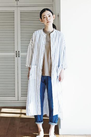 ストライプ柄のシャツワンピースを、前開きで羽織りとして活用したコーディネートです。デニムパンツとTシャツのベーシックなシンプルコーデも、ワンピースを一枚プラスするだけで雰囲気がガラリと変わります。袖をロールアップすれば、夏にも大活躍するスタイリングです。