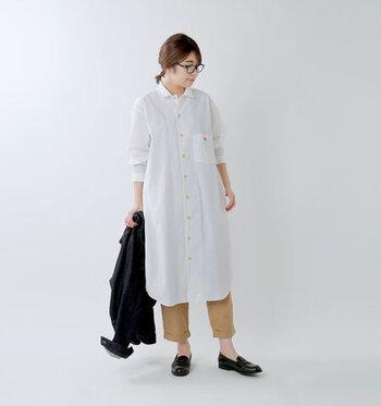 白のシャツワンピースに、ベージュのパンツを合わせたベーシックなコーディネートです。パンツは七分丈をチョイスして、さりげない肌見せで涼しげな印象を演出。足元をあえてローファーシューズにして、カジュアルになり過ぎないスタイリングにまとめています。