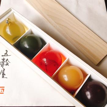 白い箱に入った玉羊羹は、まるい形と鮮やかな色が映えますね。楊枝を刺すとぷるんとみずみずしい姿をあらわします。日本茶との相性も抜群です。