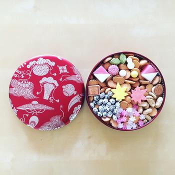 銀座で130年以上続く「銀座 菊廼舎」の冨貴寄は、雅なデザイン缶はもちろん、蓋を開けたときの驚きが魅力のお菓子。落雁やクッキー、和三盆などの小さなお菓子がぎっしりと詰まっていて、まるで宝箱のよう。