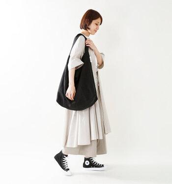 人気の黒コンバースハイカットはバッグとカラーを合わせて、コーデ全体を引き締めて。Aラインシルエットが女性らしさを引き立たせてくれますね。