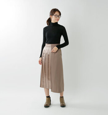 フィット感のある黒タートルと、プリーツスカートを合わせた、洗練されたコーディネート。上品コーデにメガネをプラスするとより知的な印象に仕上がります。