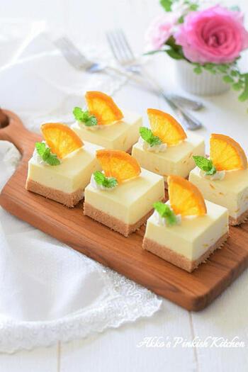 オレンジ風味のチーズケーキのトップには、オレンジの砂糖漬けを小さめにカットしたものをさして。四分の一だと大きすぎるときは、六分の一、八分の一と大きさを工夫してみましょう。  生クリームを小さく絞って、そこにミントとオレンジのスライスをアレンジしています。接着剤代わりに使えるホイップクリームの技はぜひ、覚えておきたい技のひとつです。
