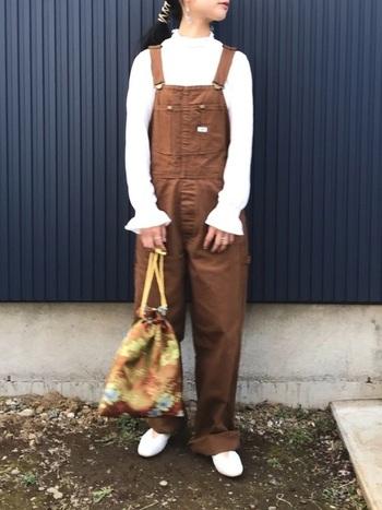 ブラウンのオーバーオールにガーリーなブラウスを合わせて可愛らしく。ジャガード柄の巾着バッグも良いアクセントになっています。