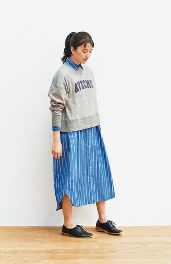 青を基調にした細みのピンストライプの爽やかなシャツワンピース。オーバーサイズのスウェットを上から着れば、いつもとは一味違った表情のレイヤードスタイルに。