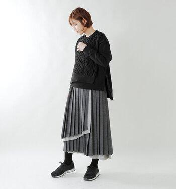 黒ニットとグレースカートを合わせたモノトーンコーデ。ロングスカートはボリュームたっぷりで、軽快な印象に。