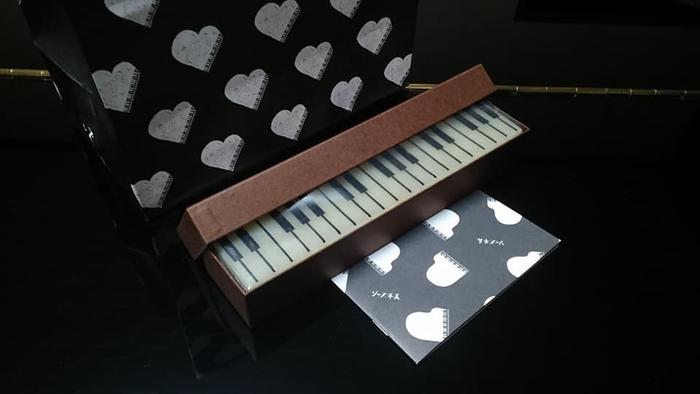 """箱を開けると、ピアノの鍵盤そっくりな羊羹が姿を現します。""""ジャズに合うように""""と誕生したこちらの羊羹は、音楽好きな方への贈り物にも喜ばれそう。"""