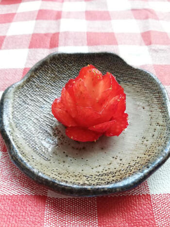 大粒の苺が手に入ったらぜひ試してほしいのが、一粒苺のお花です。苺に次々と包丁を入れていくだけの簡単レシピです。カットは下側から入れていくようにすると、上の部分まで綺麗に細かくカットを入れていくことができるので、繊細なお花の雰囲気を醸し出すことができます。  花びらを開かせた後、ミントなどのグリーンを下の部分に添えるようにすると、色のコントラストがはっきりして、本物のお花のような印象に。