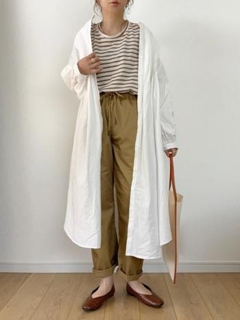 白いシャツワンピをボーダートップスとパンツに重ねて、カジュアルなレイヤードコーデに。足元はフラットシューズで女性らしいスパイスを。