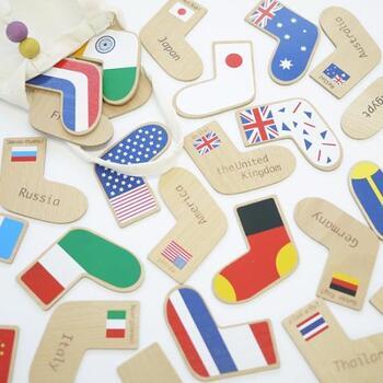 靴下の形が可愛い木製のメモリーカード。靴下には国旗、もう片方には国の名前とその国の言葉で「こんにちは」と描かれています。その右足と左足のペアを探して神経衰弱のように遊べるゲームです。