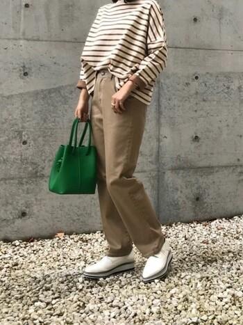 アイボリー地×ベージュのボーダートップスに、ベージュのパンツを合わせワントーンコーデに。両サイドの裾をパンツから出したり、バッグやシューズでアレンジし、コーデに抜け感をプラス!