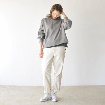 グレーのフーディースウェットトップスに、白のパンツを合わせたコーディネート。パンツの裾をさりげなくロールアップしているのがポイント。トップスの裾からはダークトーンのインナーをチラ見せして、トレンドを意識したスタイリングに。