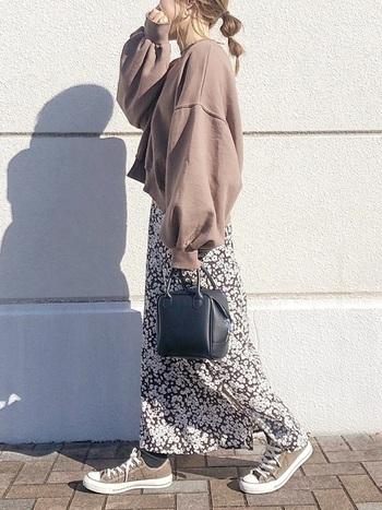 ブラウンのゆるスウェットに、同系色の花柄スカートを合わせた着こなし。スニーカーもブラウンで揃えて、全体を統一感のあるカラーリングでまとめています。小さめの黒ハンドバッグで、ブラウンをキュッと引き締める効果をプラス。
