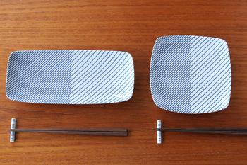 """白山陶器の""""重ね縞""""シリーズは 、長年愛され続けるロングセラー。左右で異なる線の本数とラフなタッチで、ニュアンスのあるストライプを表現しています。藍と白の縞模様がシンプルながらも存在感があり、食卓のスタメンとして頼れる存在に。"""