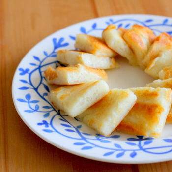 こちらは、上でご紹介した「じゃがいも餅」にチーズをアレンジしたもの。チーズでとろりとした食感がプラスされています。  ジップロックに入れて大きな四角を形作ってから焼き上げ、カットしています。つやが出るまで練り上げると、表面がなめらかなじゃがいも餅に仕上がります。
