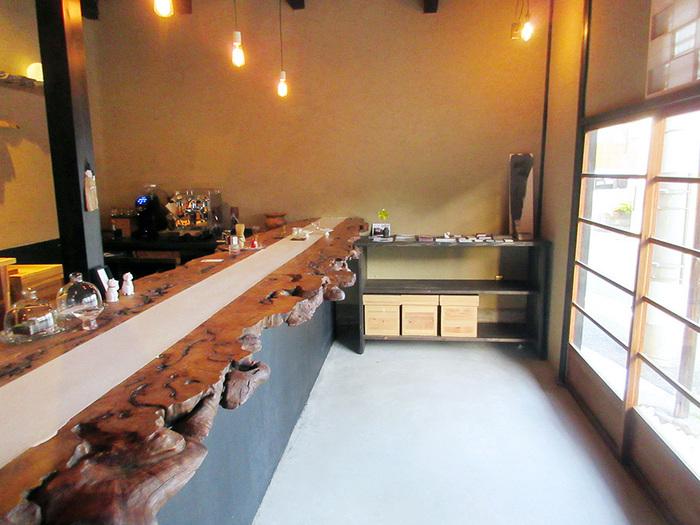 店内へ入ると目をひくのが、一枚板の長いカウンター。洗練された和モダンな空間です。スタンディング方式のカフェであり、珈琲と和菓子、そして日本酒をテーマにしたバーでもあります。