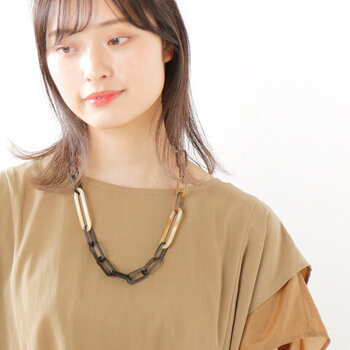 黒とベージュカラーを組み合わせた、モードな印象のチェーンネックレス。水牛の角を加工して使用し、黒や茶が混ざった自然のカラーリングを活かしたデザインが特徴です。シンプルなTシャツも、このネックレスと組み合わせるだけで格上げできます。
