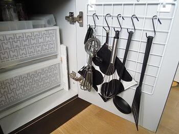 クローゼットと同様に、キッチンでも100均の吊り下げ収納が大活躍します。シンクの扉裏にフックとワイヤーネットを取り付けて、キッチンツールの収納スペースに。取り出しやすい、見せない収納。キッチンがきれいに片付きます。
