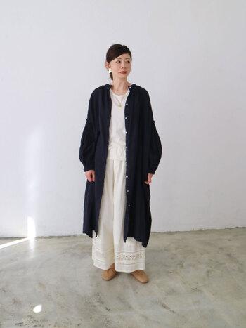 リネン素材の前あきワンピースは、ナチュラルな風合いが生かされたデザイン。端正なバンドカラーと柔らかなシルエットのバランスが、大人の女性にぴったりの一枚。ホワイトワントーンコーデ にさらりと纏って、モダンな着こなしに。