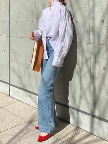ふんわりとした白のデザインシャツにフレアデニムを合わせたシンプルフェミニンコーデ。足元にレペットの赤を効かせ、レディな印象です。