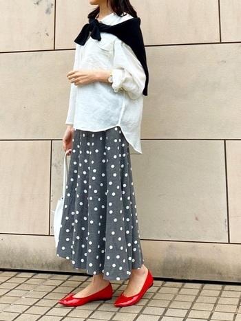 白シャツ×ドット柄のスカートに赤いバレエシューズを合わせたフレンチカジュアル風の着こなし。靴以外をベーシックカラーにすることで足元が引き立つスタイリングに。