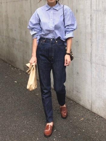 ブルーストライプシャツ×濃紺ストレートデニムのハンサムコーデ。足元に光沢のあるブラウンのローファーをチョイスして、クールな印象を和らげています。